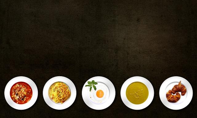 Taniere s rôznymi pokrmami na čiernom stole poukladané vedľa seba