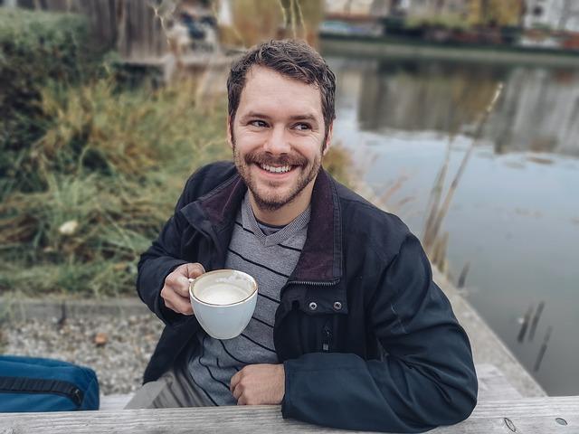 Usmiaty muž v čiernej bunde sedí pri stole vedľa jazera a pije kávu